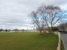 Grote uitgestrektheid van gazon met Hudson River in achtergrond, voetpad en omheining langs juiste grens royalty-vrije stock fotografie