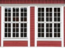 Grote vensters op een rode houten muur stock afbeeldingen