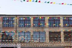 Grote vensters van de oude bouw naast het hangen van multi-colored vlaggen Stock Afbeeldingen