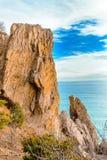 Grote verticale rots tegen het overzees en blauwe hemel met wolken royalty-vrije stock fotografie