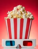 Grote vierkante doospopcorn en 3D glazen naast op helder rood Royalty-vrije Stock Afbeeldingen