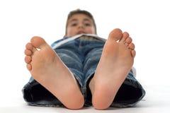 Grote voeten van een gelukkige jongen Stock Foto
