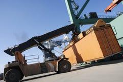 Grote vorkheftruck-vrachtwagen in haven stock foto