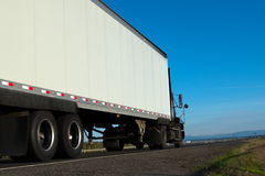 Grote vrachtwagen en aanhangwagen op de weg met horizon en blauwe hemelrug royalty-vrije stock foto
