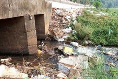 Grote vuilnisstortplaats door de weg en de rivier stock foto
