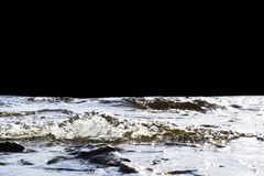 Grote winderige golven die over rotsen bespatten Golfplons in het meer op zwarte achtergrond Golven die op een steenachtig strand Stock Fotografie
