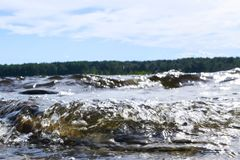 Grote winderige golven die over rotsen bespatten Golfplons in het meer tegen strand Golven die op een steenachtig strand breken,  Royalty-vrije Stock Foto