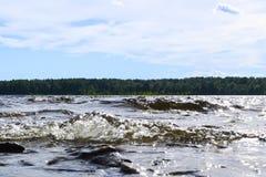 Grote winderige golven die over rotsen bespatten Golfplons in het meer tegen strand Golven die op een steenachtig strand breken,  Stock Foto