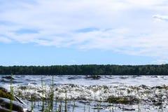 Grote winderige golven die over rotsen bespatten Golfplons in het meer tegen strand Golven die op een steenachtig strand breken,  Royalty-vrije Stock Afbeelding