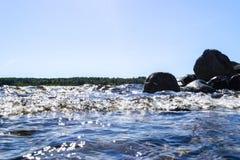 Grote winderige golven die over rotsen bespatten Golfplons in het meer tegen strand Golven die op een steenachtig strand breken,  Stock Afbeeldingen