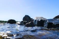 Grote winderige golven die over rotsen bespatten Golfplons in het meer tegen strand Golven die op een steenachtig strand breken,  Stock Fotografie