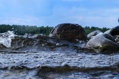 Grote winderige golven die over rotsen bespatten Golfplons in het meer tegen strand Golven die op een steenachtig strand breken,  Stock Afbeelding