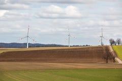 Grote windmolens voor windenergie dichtbij het dorp met gebieden en weiden royalty-vrije stock afbeelding