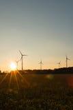 Grote Windturbines in zonsondergang Stock Foto's