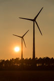 Grote Windturbines in zonsondergang Stock Foto