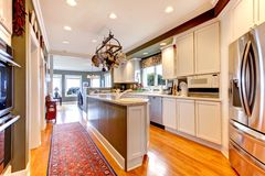 Grote witte en groene keuken met hardhoutvloer. Stock Afbeeldingen