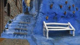 Grote witte houten bank dichtbij de treden onder de blauwe muren van Royalty-vrije Stock Fotografie