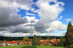 Grote witte wolken in de blauwe hemel boven een dorp in Beieren Stock Foto