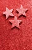 Grote zilveren sterren op heldere rode glitteryachtergrond Stock Foto's