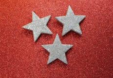 Grote zilveren sterren op heldere rode glitteryachtergrond Stock Afbeelding