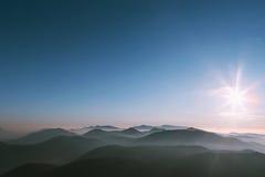 Grote zonsondergang op bergen met mist Royalty-vrije Stock Foto
