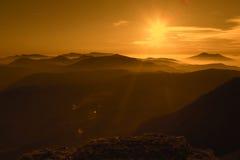 Grote zonsondergang op bergen met mist Stock Afbeelding