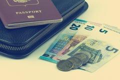 Grote zwarte beurs en een rood paspoort Een paar Euro rekeningen en muntstukken Zachte fotoverwerking royalty-vrije stock foto