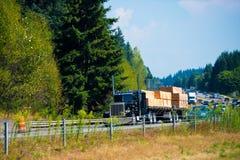 Grote zwarte klassieke semi de krommeweg van het vrachtwagentimmerhout Royalty-vrije Stock Foto's