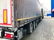 Grote zwarte vrachtwagen, wagen met een aanhangwagen met canvas het afbaarden en een groot aantal wielen stock foto