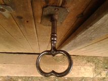 Grotere oude versleten zwarte glanzende sleutel in eiken houten stoffige kelderdeur, close-up van hierboven, in daglicht Stock Afbeeldingen