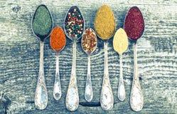 Groteska metallskedar med olika sorter av kryddor på gammalt trä Royaltyfri Bild