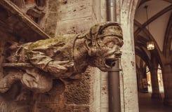 Grotesque schnitzte das Aufwachen der menschlichen Figur, die von der Gosse eines Gebäudes, Steinwasserspeier auf Gebäude im Baye Stockfoto