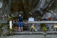 Grotta della caverna di Lourdes con i fiori e le candele fotografie stock libere da diritti