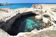 Grotta Della Poesia. SALENTO, ITALY - JUNE 1, 2017: People visit Grotta Della Poesia swimming cave in Roca, Salento Peninsula, Italy. With 50.7 million annual royalty free stock images