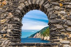 Grotta di Lord Byron with blue water and coast with rock cliff through stone wall window, Portovenere town, Ligurian sea, Riviera stock photo