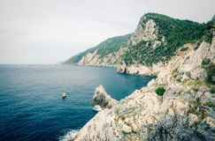 Grotta di Lord Byron with blue water, coast with rock cliff, yellow boat and blue sky near Portovenere town, Ligurian sea, Riviera. Di Levante, National park royalty free stock image