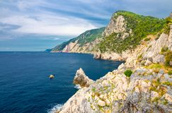 Grotta di Lord Byron with blue water, coast with rock cliff, yellow boat and blue sky near Portovenere town, Ligurian sea, Riviera. Di Levante, National park stock images
