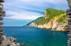 Grotta di Lord Byron with turquoise water and coast with rock cliff through stone wall window, Portovenere town, Ligurian sea, Riv royalty free stock photography