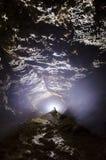 Grottaentracne med ljus och stalagmit Arkivfoto
