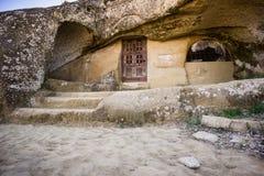 Grottahus med den gamla trädörren arkivbild