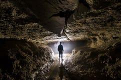 Grottatunnelbana med manspeleologen och ljus på ingången Royaltyfri Bild