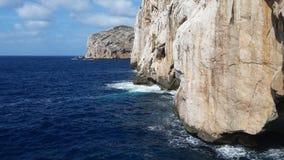 Grotto del Nettuno - Neptun's cave Sardinia. The bright blue sea at the level of the entrance in Neptun's Cave in Sardinia stock image