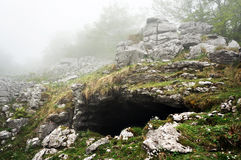 Grotto entrance in mountain Stock Images