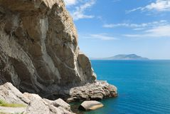 Grotto at the foot of the mountain in the sea. Royalty Free Stock Photo