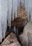 Grottoes and cracks in the rock with icicles. Royalty Free Stock Images