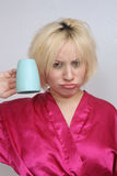 Grouchy Blonde with an Empty Coffee Cup. A disheveled frowning blonde wearing a bathrobe, holds an empty coffee cup upside down stock images