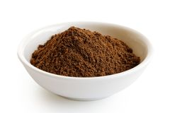 Ground allspice in white ceramic bowl. royalty free stock images