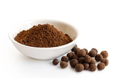 Ground allspice in white ceramic bowl isolated on white. Whole a stock photos