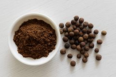 Ground allspice in white ceramic bowl isolated on white wood background from above. Whole allspice. royalty free stock image
