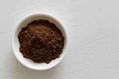 Ground allspice in white ceramic bowl on white wood bac royalty free stock image